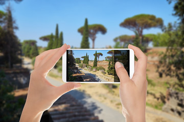 A man is making a photo of the road between ruins in Pompeii on a summer sunny day on a mobile phone