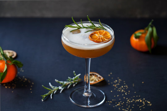 Christmas cocktail of amaretto sour with dehydrated clementine and rosemary