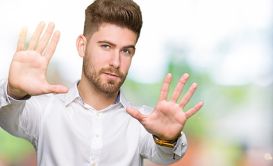 Young handsome business man Smiling doing frame using hands palms and fingers, camera perspective
