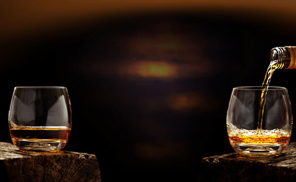 Pour whiskey out of the bottle in whiskey glass in the bar