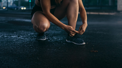 Close-up Shot of Beautiful Confident Fitness Girl Ties Shoelaces. She is in an Urban Environment Under a Bridge with Cars in the Background.