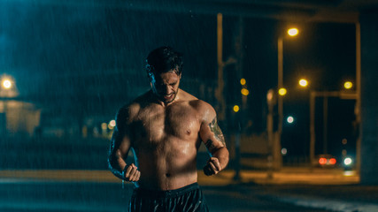 Shirtless Athletic Muscular Young Man is Celebrating His Sport Accomplishments on a Rainy Night and Showing His Muscles. He is in an Urban Environment Under a bridge with Cars in the Background.