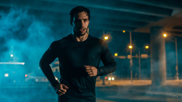 Sweating Tired Athletic Muscular Young Man in Sports Outfit Jogging in a Street Filled With Smoke. He is Running in an Evening Urban Environment Under a bridge.