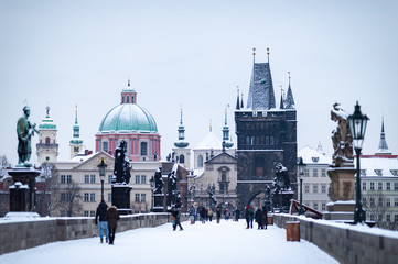 Old Town Bridge Tower by the famous Charles Bridge. The city of Prague covered with snow. Photo with low depth of field.