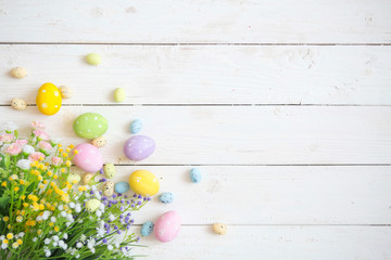 Easter eggs with flowers on white rustic wooden background. View from above