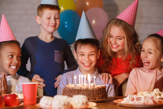 Boy celebrating birthday and making wish at home