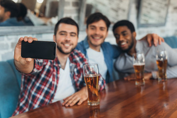 Men taking selfie and drinking beer in bar
