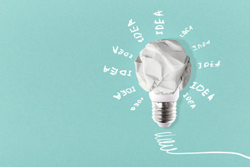 Wall Mural - crumpled white paper lightbulb with inscription idea around on a blue background