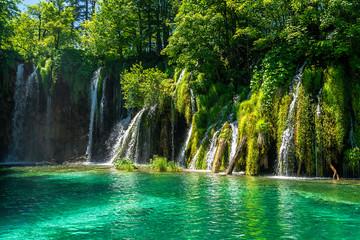 Die Plitvicer Seen sind der älteste und größte Nationalpark in Kroatien. Im Bildmittelpunkt sind Wasserfälle im Vordergrund ein See im Hintergrund sind Bäume