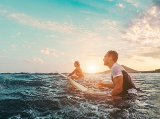 Fit couple surfing at sunset