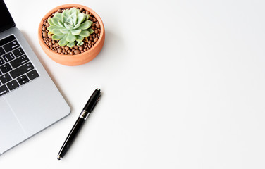 Top view of laptop Succulent and pen on white background with copy space