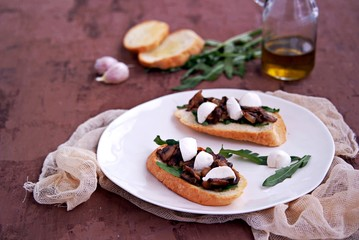 Light snack, crispy bruschetta with champignons, arugula and mozzarella. Italian Cuisine.