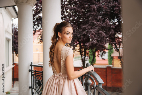 d4a607e8b Young model with great evening dress stand by the restaurant. Brunette girl  has beautiful hair style and makeup