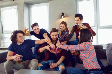 A group of friends with mugs and popcorn at a party indoors