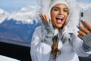 Smiling young woman in white coat and fur hat taking selfie outdoors