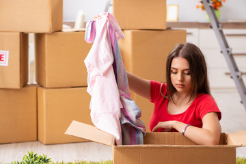 Young beautiful woman moving to new flat