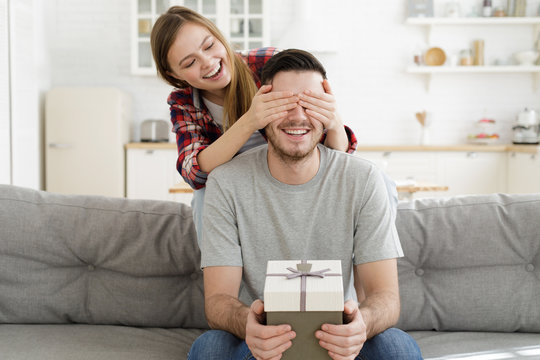 Woman presenting gift for her boyfriend, closing his eyes with hands to make surprise