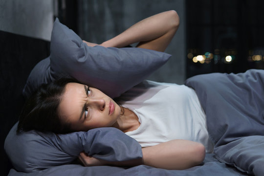 Photo of annoyed young woman unable to fall asleep because of loud neighbors
