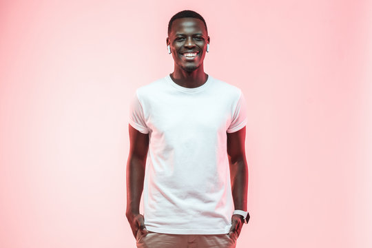 Young african american man standing with hands in pockets, wearing blank white t-shirt with copy space for your logo or text, isolated on pink background