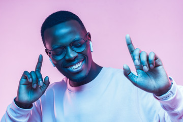 Portrait of happy young african man listening to music with wireless earphones isolated on pink background