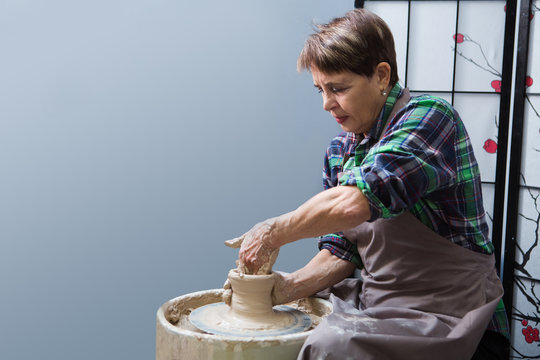 Senior woman in casual clothes and aprons making ceramic pot on pottery wheel in workshop. hobby on pension