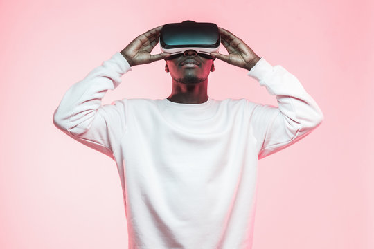 Young african man holding virtual reality goggles with both hands, isolated on pink background
