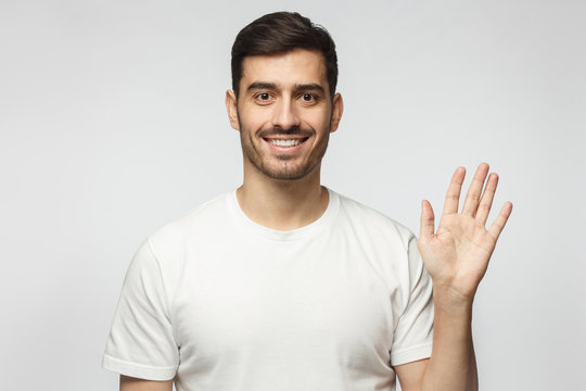 European man greeting someone with open hand, smiling, enjoying communication, isolated on gray background