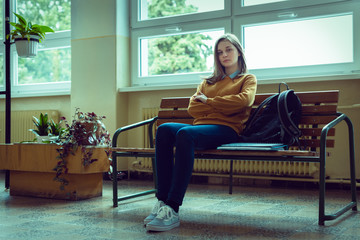 Young anxious and depressed female college student sitting in the hallway at her school. Education, Bullying, Depression, Stress concept.