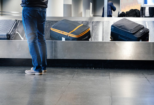Rear view of a man preparing to take luggage from the conveyor belt in modern Airport