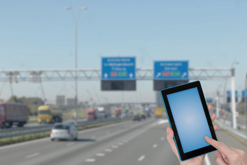 Riding a highway  infographic concept. Finger touching tablet blue blank screen ready for your text. Intentionally blurred image of a motorway in the background. All potential trademarks are removed