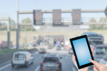 Traffic jam infographic concept. Finger touching tablet blank screen ready for your text. Intentionally blurred image of starting traffic jam in the background. All potential trademarks are removed
