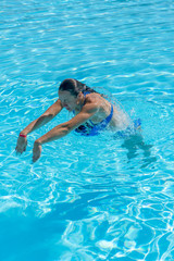 Woman diving in the swimming pool. Young beautiful girl swimming in pool. Brunette relaxing in clear warm water on sunny day. Top view Close up Slow motion. vertical photo.