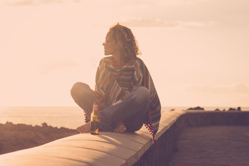 Attractive strong independent woman sit down on a wall barefoot and hippy style looking at the nature around and enjoying a golden outdoor leisure lifestyle sunset near ocean - coloured lifestyle