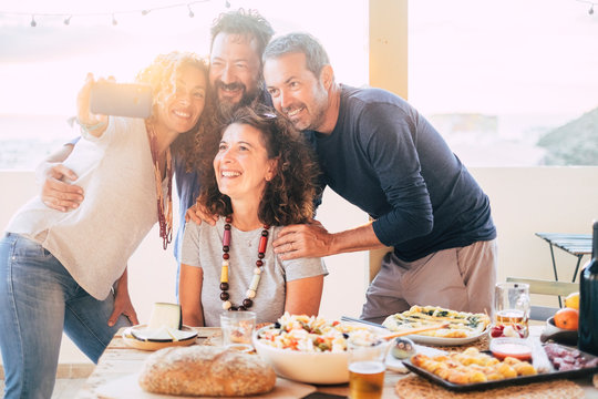 Group of friends have fun together during a lunch outdoor in the terrace at home and taking a modern selfie with smart phone to share on social media accounts for internet life - happy adult people