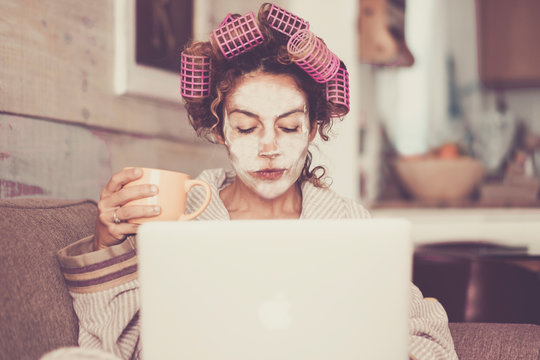 Rare and funny portrait of beautiful woman with facial mask and curlers hair taking a coffee at home while use internet with modern laptop computer - home scene for modern lifestyle people