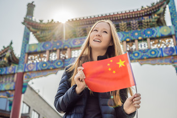 Enjoying vacation in China. Young woman with national chinese flag on the background of the old Chinese street. Travel to China concept. Visa free transit 72 hours, 144 hours in China