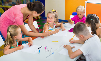 Kids drawing together with tutor at hobby group