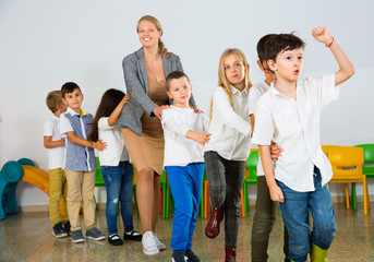 Positive  female teacher playing circle game with children in classrom