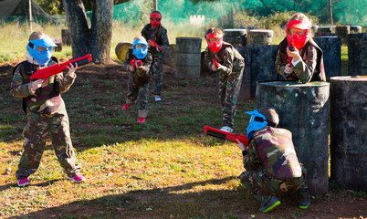 Children paintball players of opposite teams playing in shootout outdoors