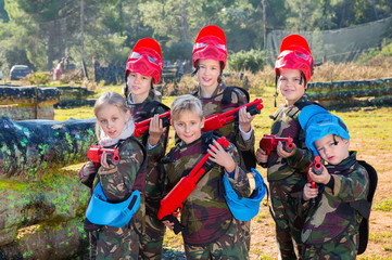 Friendly group of children paintball players in camouflage posing with guns on paintball playing field outdoors
