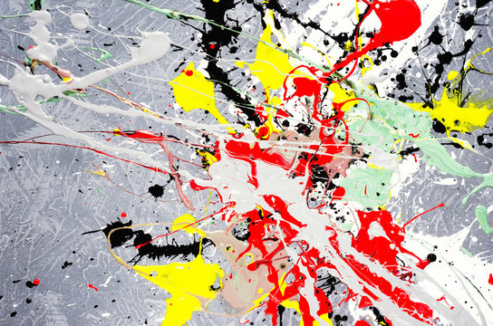 a spot of white and black and yellow and green and red spilled paint on a concrete textured surface