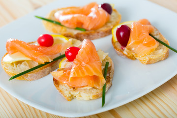 Tapas with salmon, lemon, cranberry
