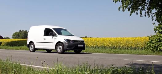 Minivan vom Kundendienst fahrend auf einer Landstraße