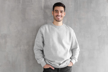 Young man in oversized sweatshirt isolated on textured gray wall background Wall mural