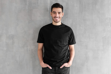 Mock up of young man body in empty black t-shirt isolated on textured gray wall background