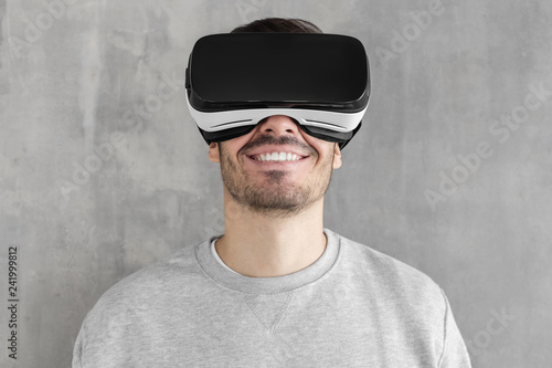 ca5ea1ad63a Close-up portrait of smiling handsome man playing video games in VR goggles  or 3d