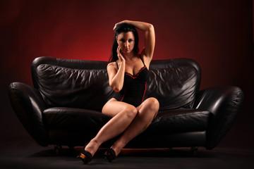 Schwarzhaarige Frau posiert auf Sofa
