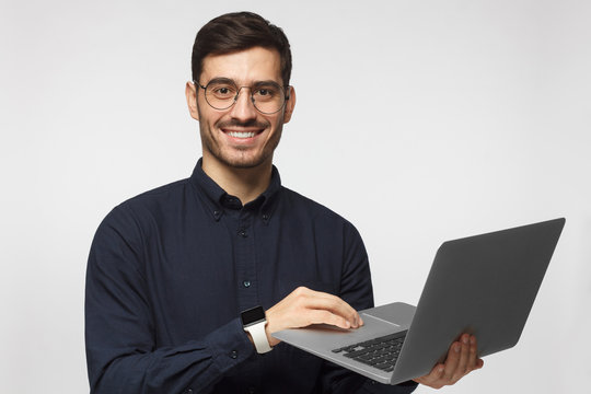 Young confident business man in deep blue shirt holding laptop and smiling at camera, isolated on gray background