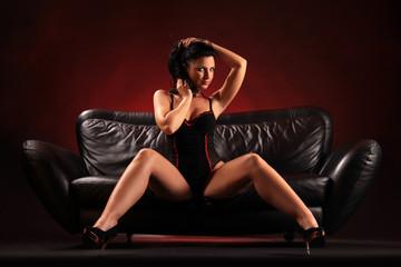 Verführerisch posierende Frau auf Sofa sitzend