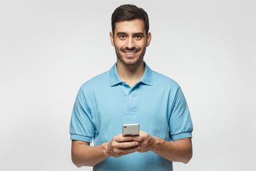 Young smiling man standing isolated on grey background, looking at camera, holding phone with both hands
